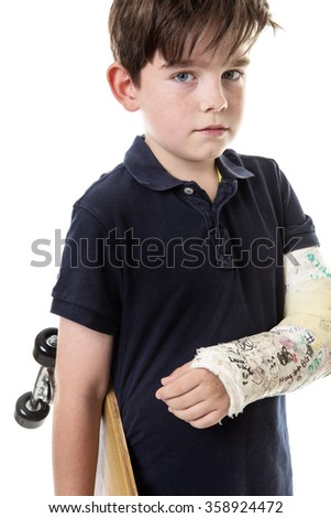 Young boy is unable to use his skateboard because he has broken his arm - stock photo