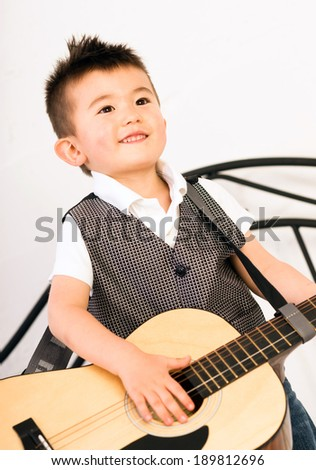 Young Boy Jamming Full Size Guitar Gritting Teeth Playing Musician - stock photo