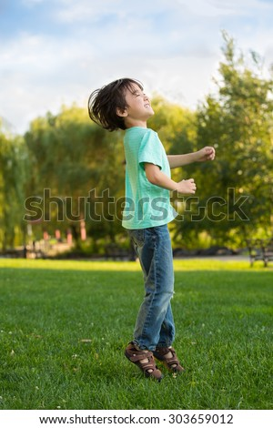 Young boy jumping for joy in a park on the grass. Excited little boy with joyful expression outside. Six year old half Asian child elated, happy, ready to go back to school. Action shot of jumping boy - stock photo