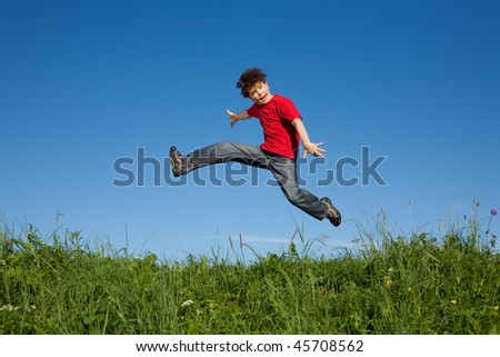 Young boy jumping outdoor against blue sky