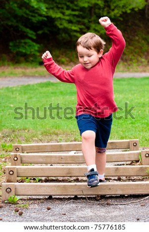 Young boy jumping over obstacle on exercise trail - stock photo
