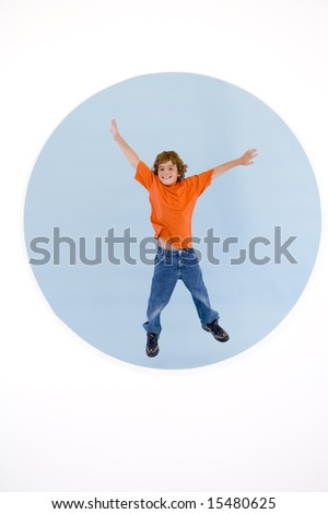 Young boy jumping with arms out smiling - stock photo