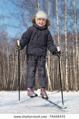 Young boy jumps and crosses cross-country skis inside winter forest at sunny day - stock photo