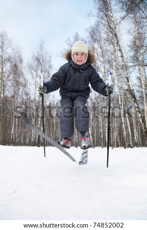 Young boy jumps on cross-country skis inside winter forest at sunny day - stock photo