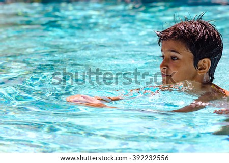 Young boy kid child eight years old swimming in pool having fun leisure activity