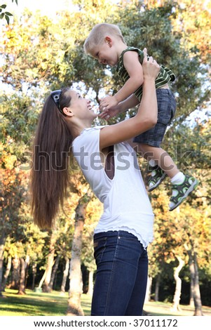 Young boy laughing on mother's arms at park