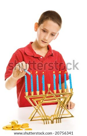 Young boy lighting the menorah for Hanukkah.  Isolated on white. - stock photo