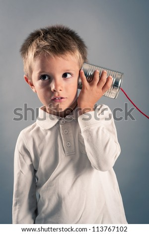 Young boy listen to tin can telephone. - stock photo