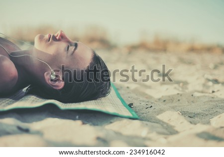 Young boy listening music at headphones on beach  - stock photo