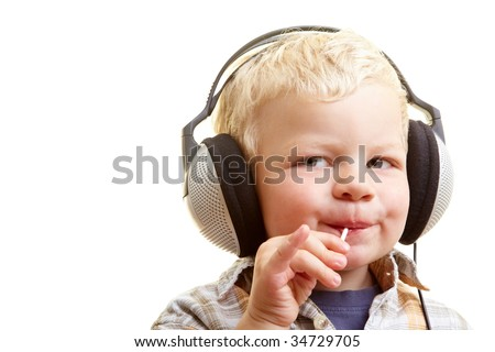 Young boy listening to music and sucking on a lollipop