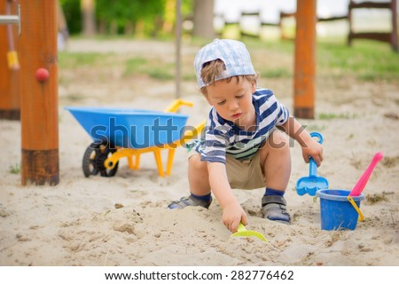Young boy / Little kid playing around the playground - stock photo