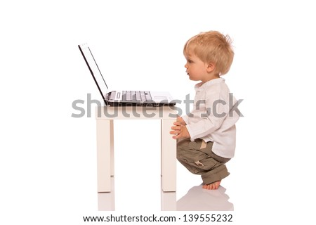 Young boy looking at a laptop on a stool. Isolated on white background - stock photo