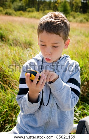 young boy looking at gps while geocaching