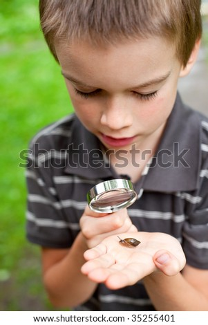Young boy looking at snail through hand magnifier, focus on snail - stock photo