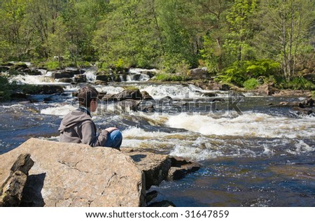 young boy looking at water rapids (The Falls of Dochart, Scotland) - stock photo