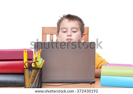 Young Boy Looking Down at Laptop Computer Screen While Studying at Desk with Pencil Holder and Supplies and Surrounded by Colorful Books and Binders, in Room with White Background and Copy Space - stock photo