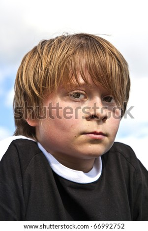 young boy looking seriously and critical - stock photo