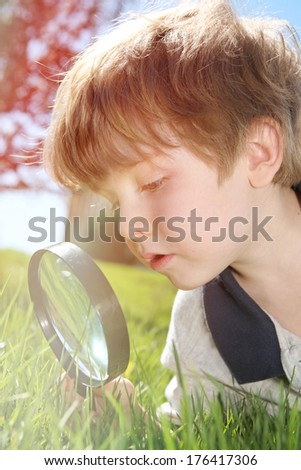 Young boy looking through a magnifying glass - stock photo
