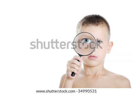 young boy looking through a magnifying glass over white