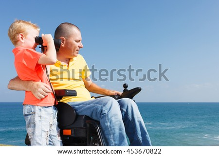 Young Boy Looking Through Binoculars While His Disabled Father - stock photo