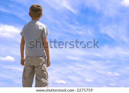Young boy looking up towards blue sky with clouds. - stock photo