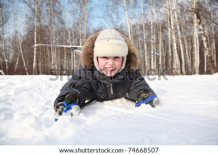 Young boy lying in cross-country skis and poles and smiling inside winter forest at sunny day - stock photo
