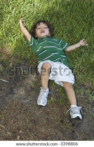 Young boy lying on grass looking up at the camera