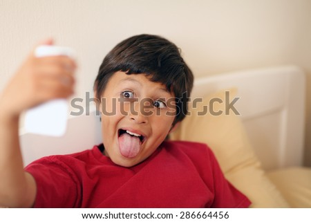 Young boy making selfie pictures with smart phone - with shallow depth of field - stock photo