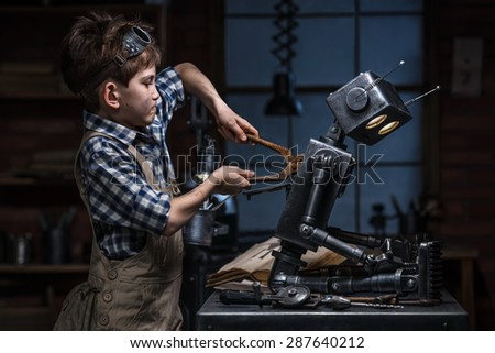 Young boy mechanic repairing the robot in the workshop at night