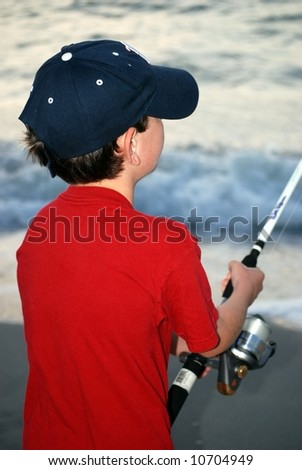 Young boy ocean fishing from the beach at dusk. - stock photo