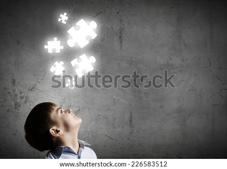 Young boy of school age looking at puzzle elements - stock photo