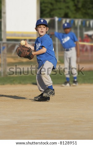 young boy on a baseball field with ball in hand - stock photo