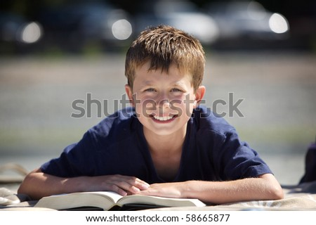 young boy on a beach reading a book - stock photo