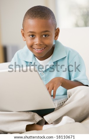 young boy on bed using laptop - stock photo