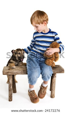Young boy on bench and puppy - stock photo