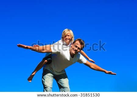 Young boy on father's back playing airplane outdoors - stock photo