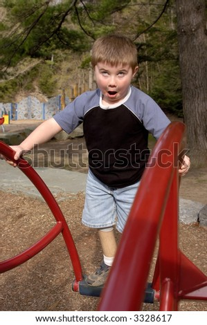 Young boy on playground equipment with a dizzy expression
