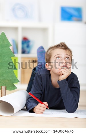 Young boy on the floor thinking on a drawing concept - stock photo