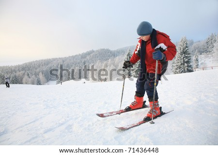 Young boy on the slope of a downhill ski run - beginner.