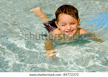 Young boy or kid swimming in shallow pool during vacation. - stock photo