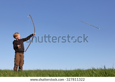 Young boy outdoors with bow and arrow - stock photo