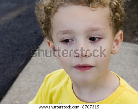 Young boy outside giving sideways curious look - stock photo