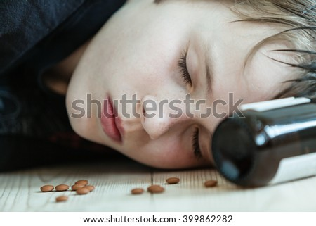 Young boy passed out on drugs and alcohol or dead after committing suicide lying on the floor with an empty medication bottle at his head and capsules around his face - stock photo