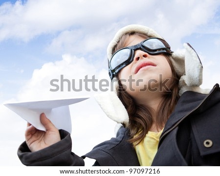 Young boy pilot holding a paper airplane looking at the sky - stock photo