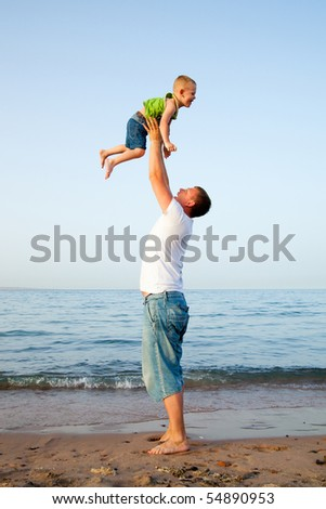 Young boy play with father. Father throwing his son into the air. On a beach. - stock photo