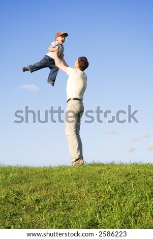 Young boy play with father. Green grass. Blue sky. 5 - stock photo