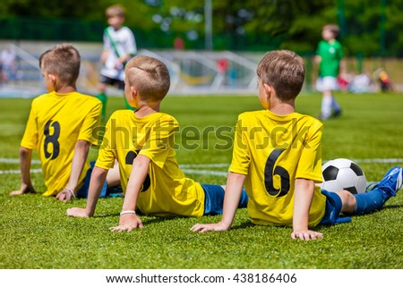 Young boy player waiting for a kick ball. Young boys in soccer team sitting together on the sports field. Kids as a reserve soccer football players. Football soccer match tournament for children teams - stock photo
