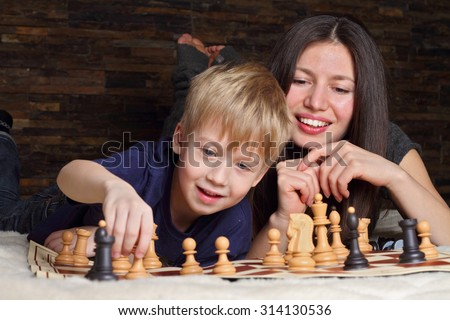 Young boy  playing chess with his Babysitter.  Educated nanny concept.  - stock photo