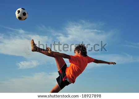 Young boy playing football - low angle view - stock photo