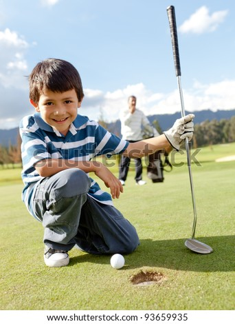 Young boy playing golf at the club - stock photo